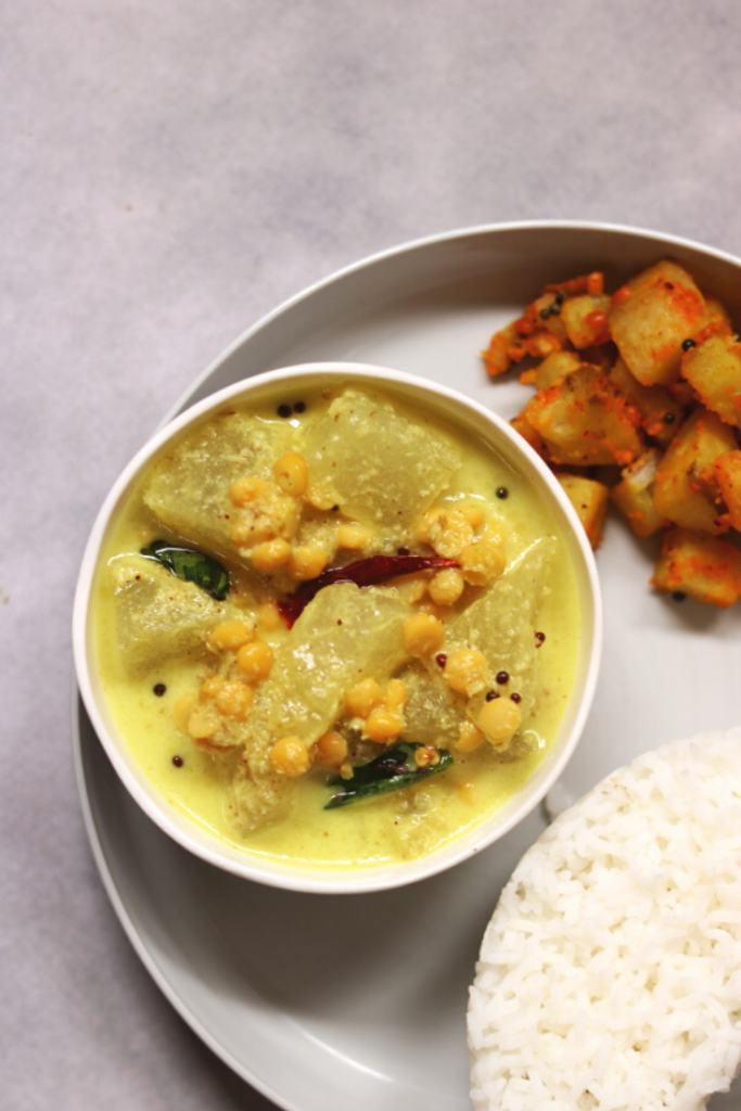 Poosanikai Kootu is a mellow curry of Ash Gourd (Winter Melon) and Split Bengal Gram flavoured with a coconut-green-chilli-cumin paste