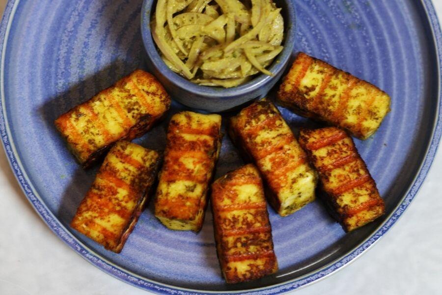 Pan Grilled Paneer called Hariyali Paneer Tikka. The paneer has been marinated in a paste made of hung curd coriander, mint, lemon juice, chaat masala, and other ingredients.