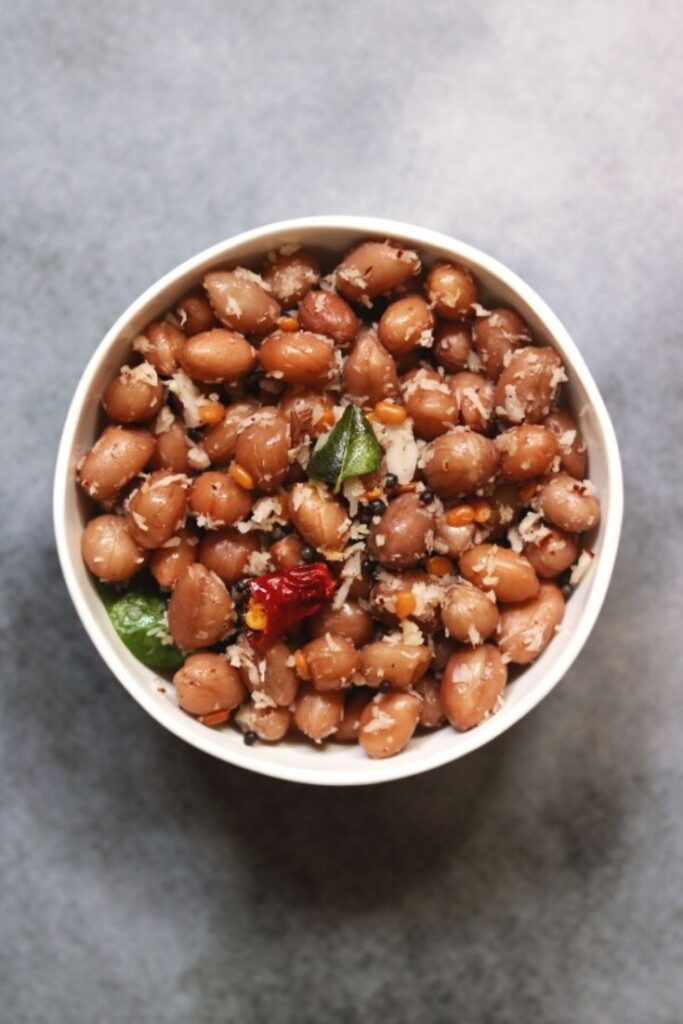 A bowl of boiled peanuts flavoured with coconut. This snack is called Peanut Sundal, Verkadalai Sundal or Palli Guggillu in various parts of India.