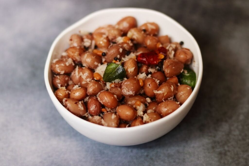 A bowl of Verkadalai Sundal, called Palli Guggillu in Telugu, is a snack of tempered boiled peanuts with grated coconut.