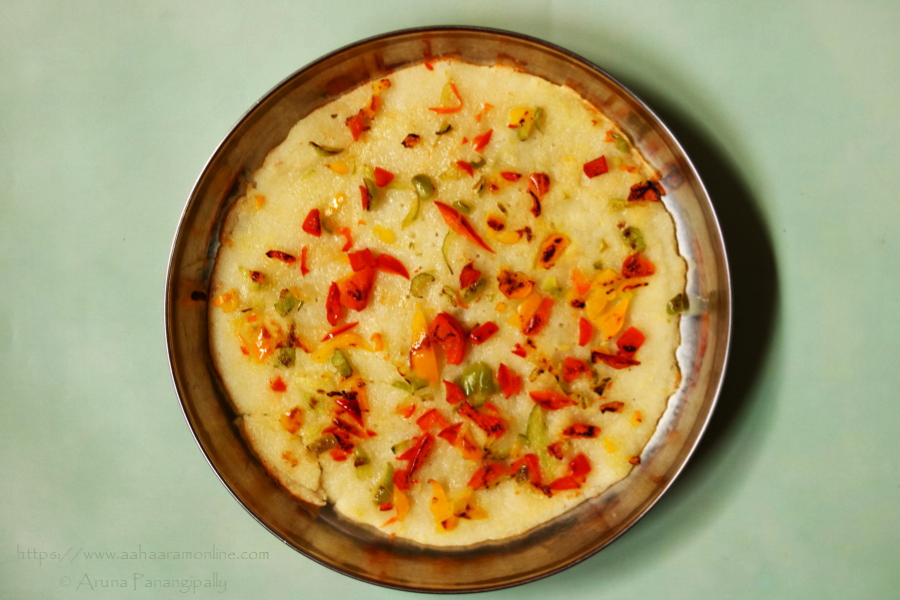 Rava Uttapam: Semolina Pancake topped with red, yellow, and green bell peppers.