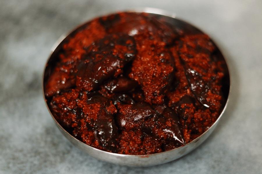 Andhra-style Brinjal Pickle or Vankaya Nilava Pachadi: Fried brinjal pieces pickled with mustard, fenugreek, chilli powder, and oil.