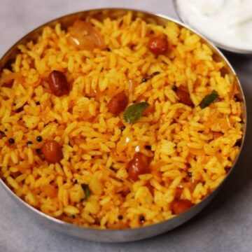 A Bowl of Phodnicha Bhaat, the Maharashtrian Seasoned Fried Rice, with Cucumber Raita