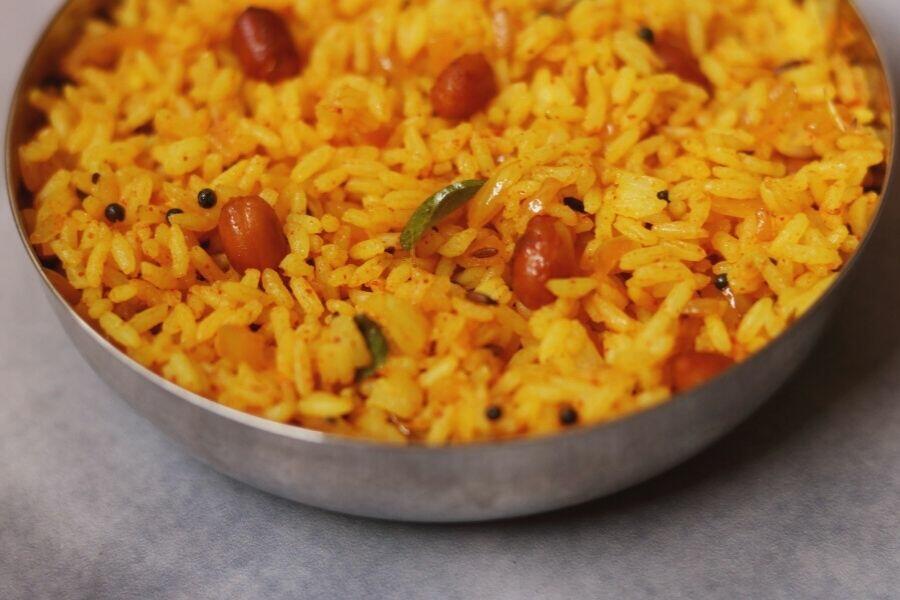A close up of a bowl of Phodnicha Bhat, the Maharashtrian Seasoned Rice